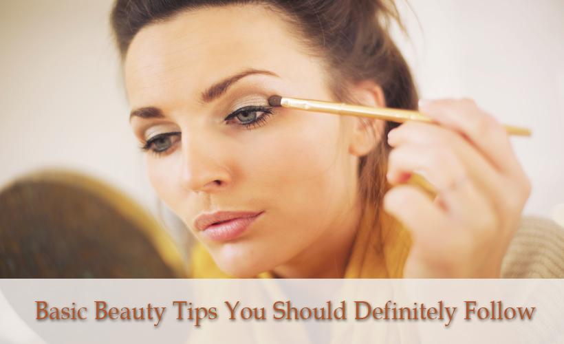 attractive woman applying makeup while looking at the mirror Hpmg1 UVYx - Basic Beauty Tips You Should Definitely Follow