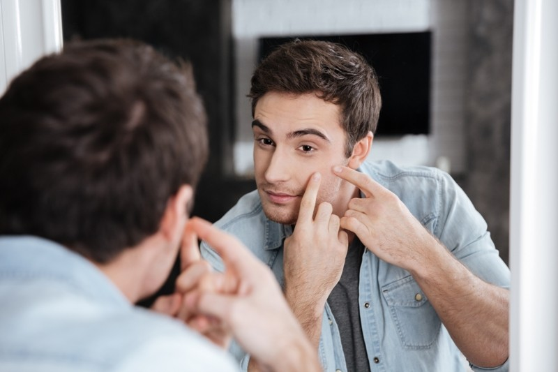 graphicstock close up portrait of a man looking at himself in a mirror and squeezing his pimples BdhD 2L2e - 7 Simple Ways to Use Hydrogen Peroxide to Treat Acne