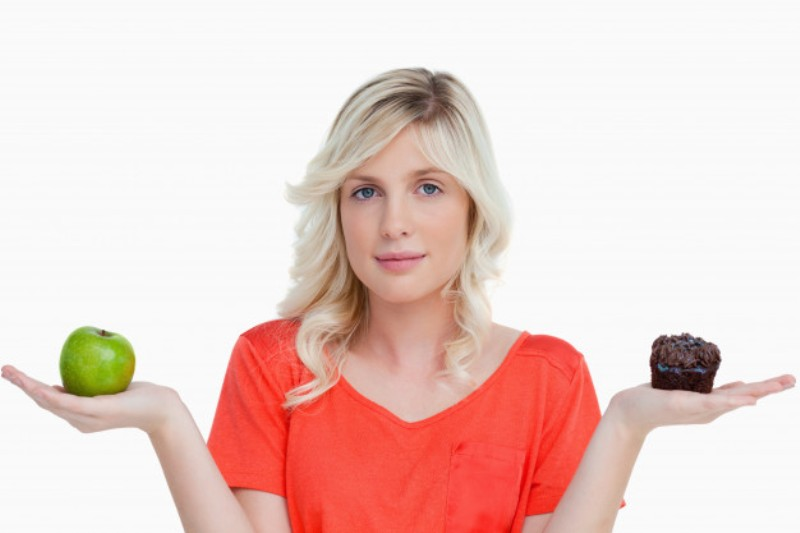 young woman looking camera while holding muffin green apple 13339 208143 - Nagendra Gadamsetty